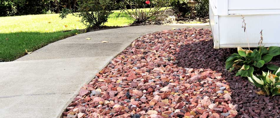 Rock mulch installed in a landscaping bed beside a sidewalk at a residential property.